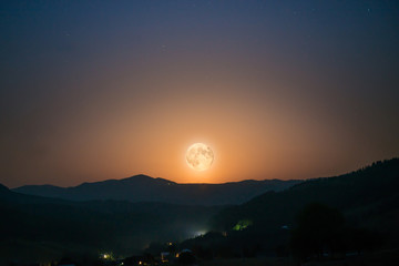 Big moon rising on night sky