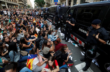 People sit during a protest as Catalan regional police officers stand guard outside National Police station, in Barcelona