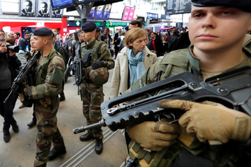 French Defense Minister Florence Parly walks with French soldiers as they patrol in the Montparnasse train station in Paris
