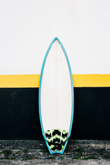 One Surfboard Leaning Against Black Yello White House Facade