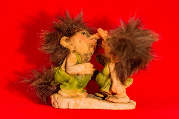 Funny shaggy troll toy from Norway on a red background