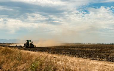 Tractor Plowing Dusty Field