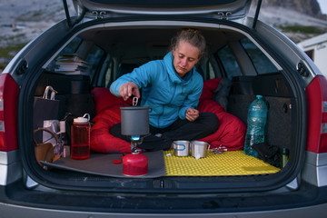 Woman cooking in the back of the car