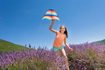 Happy girl running with kite in lavender field