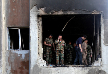 Syrian army soldiers stand in a damaged building at a site where suicide bombers attacked a police station in Damascus