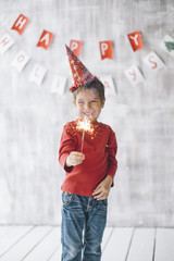Little smiling boy holding sparkler