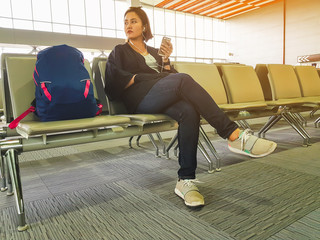 casual woman with backpack sitting in airport hall while waiting for her flight. Young Asian girl check flight number on mobile phone and listen music in airport