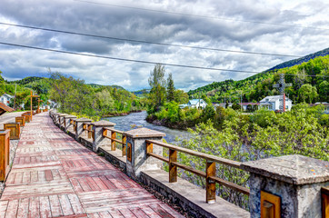 Wooden boardwalk terrace sidewalk painted red by river in Quebec village