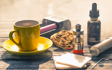 Still life with electronic cigarette with botle and coffe on the wooden background