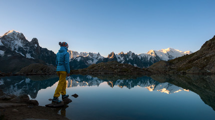 Woman standing at the lake admiring the sunrise over mountains
