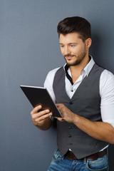 mann steht vor grauer wand und schaut auf sein tablet