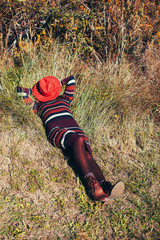 Anonymous woman hiding her face with a hat lying on the grass.