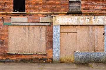 Abandoned shop with blocked up windows and doors in a street in Belfast