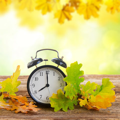 Autumn time - fall leaves with alarm clock on table in fall garden