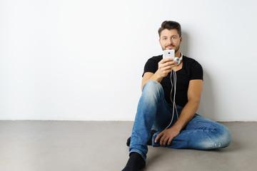 mann sitzt auf dem fußboden und hört musik