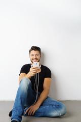 lachender mann sitzt auf dem boden und hört musik