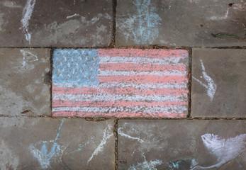 An American Flag on a sidewalk.