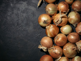 Fresh yellow onions on black concrete background. Onions with copy space. Fresh onions in low key. Hard light. Top view.