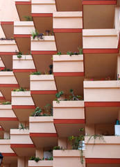 pink balconies on modern apartment building with house plants