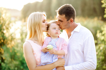Happy young family spending time together in green nature park. wife with husband and little baby. Mother and father kissing baby