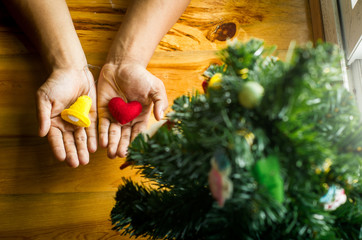 Man holding heart and bell in hands for decorate Christmas tree