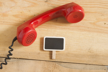 Red old fashioned telephone receiver on wooden table