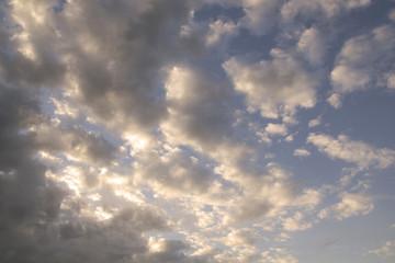 sun and cumulus white clouds against a beautiful blue sky