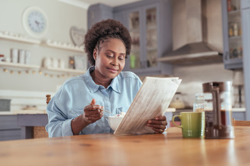 Young woman reading the newspaper while eating breakfast at home