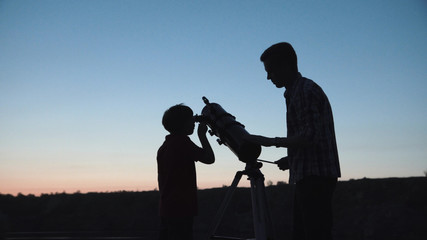 Anonymous man with little boy looking through telescope in twilight. Wall mural