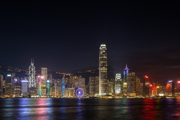 Hong Kong Island's skyline over Victoria Harbour with lit modern skyscrapers at night in Hong Kong, China. Viewed from Tsim Sha Tsui, Kowloon. Copy space.