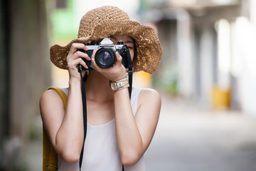 Asian tourist using camera with blurry city background