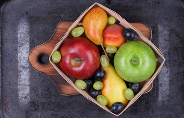 Red apple, dark blue grapes, green apple, yellow pear, green grapes, orange peach in a wooden box on a metallic background in retro style