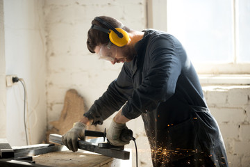 Worker in workwear, protective glasses, hearing protection headphones, gloves using dangerous electric power tools in loft workshop. Safety at workers workplace, personal protective equipment concept Wall mural