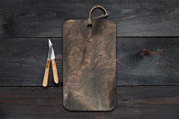 Wooden background with empty board and knives