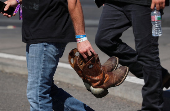 A man wearing a 3 day admission wristband to the Route 91 Harvest music festival carries cowboy boots near the scene of a mass shooting in Las Vegas