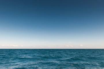 бирюзового цвета море с горизонтом и облаками