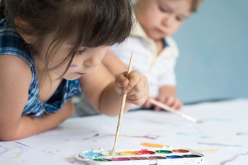 Children playing and painting at home or kindergarten or playschool