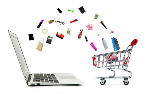 Shopping cart and laptop computer with products isolated on white background, shop online concept.