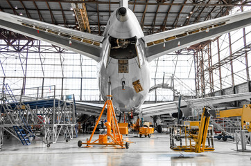 Large passenger aircraft on service in an aviation hangar rear view of the tail, on the auxiliary power unit.