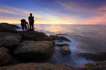 two photographer taking landscape of sea and wave on the rock during sunset