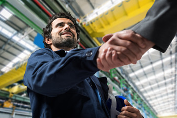 Men shaking hands in an industrial facility