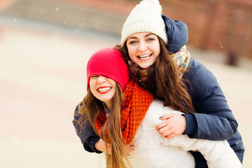 Happy brightful positive moments of two stylish girls hugging on