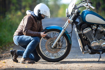 Woman repairing a spoked wheel on a motorcycle on a dirt countryside road