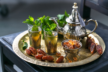 Moroccan mn tea in traditional glasses with mint, dates and sugar