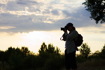 silhouette of a photographer in sunset at countryside