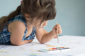 Four years child is painting at home. Beautiful little girl with paint brush and watercolor.