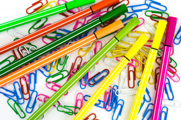 multicolored paper clips and markers randomly scattered on white paper, abstract background