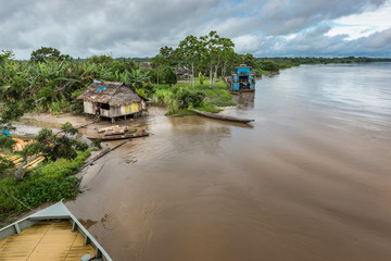 Wide view of Amazon shack and large blue boat on river