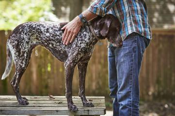 a man petting his dog