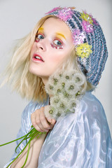 Young girl in sparkling hat with dandelions